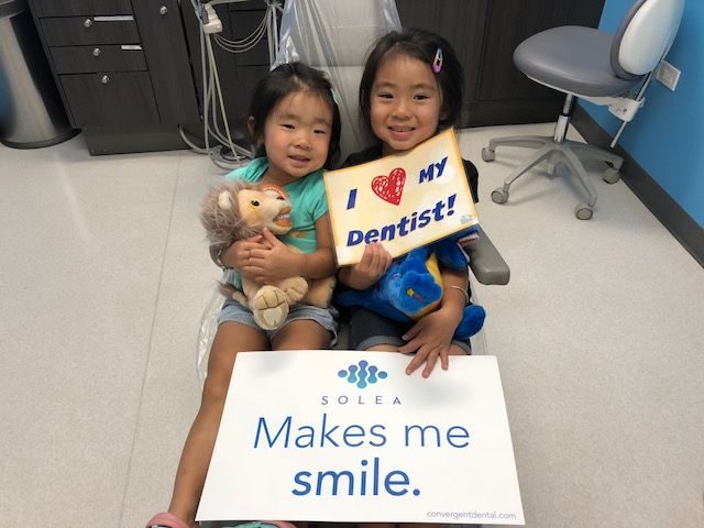 Two girls smiling and holding placards at Oahu Pediatric Dentistry