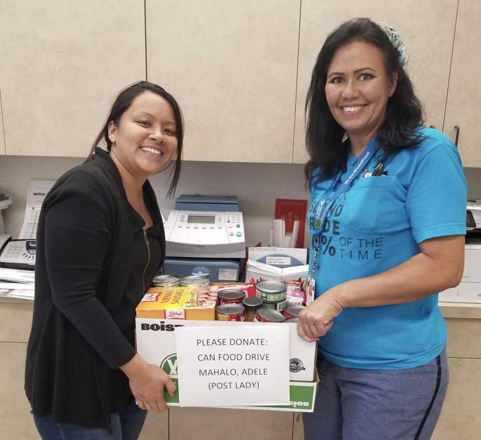 Two dental hygeinist holding the donation box Oahu Pediatric donated to NACL hunger food drive