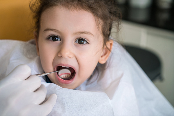 Dentist examining little girls teeth